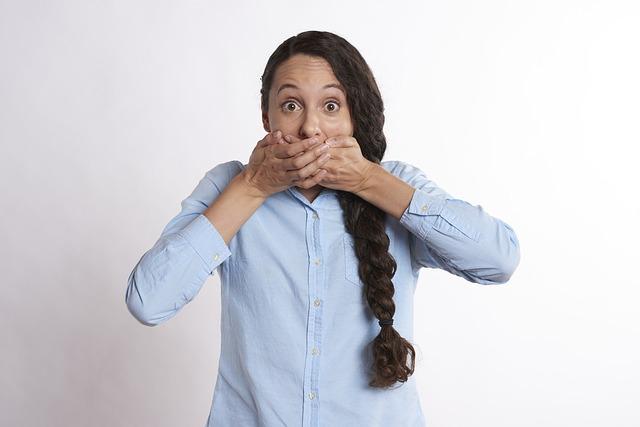 口をふさいでいる女性